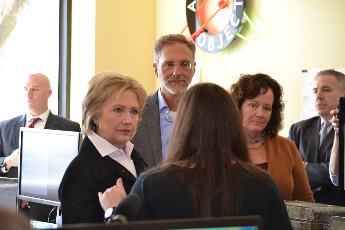Atomic CEO Carl Erickson, Business Manager Mary O'Neill and Hillary Clinton speaking with Designer Kim Wolting