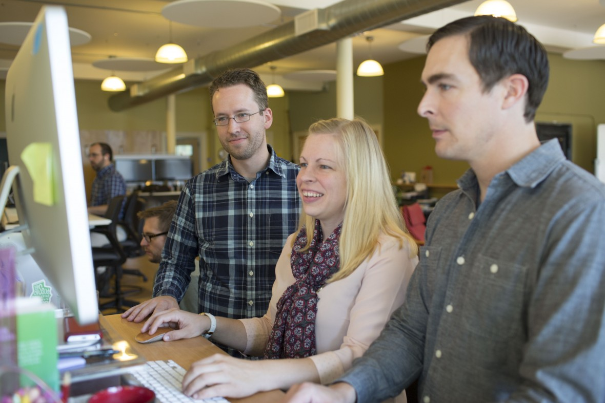 A photo of three Atomic Object employees working together in front of a computer in Grand Rapids
