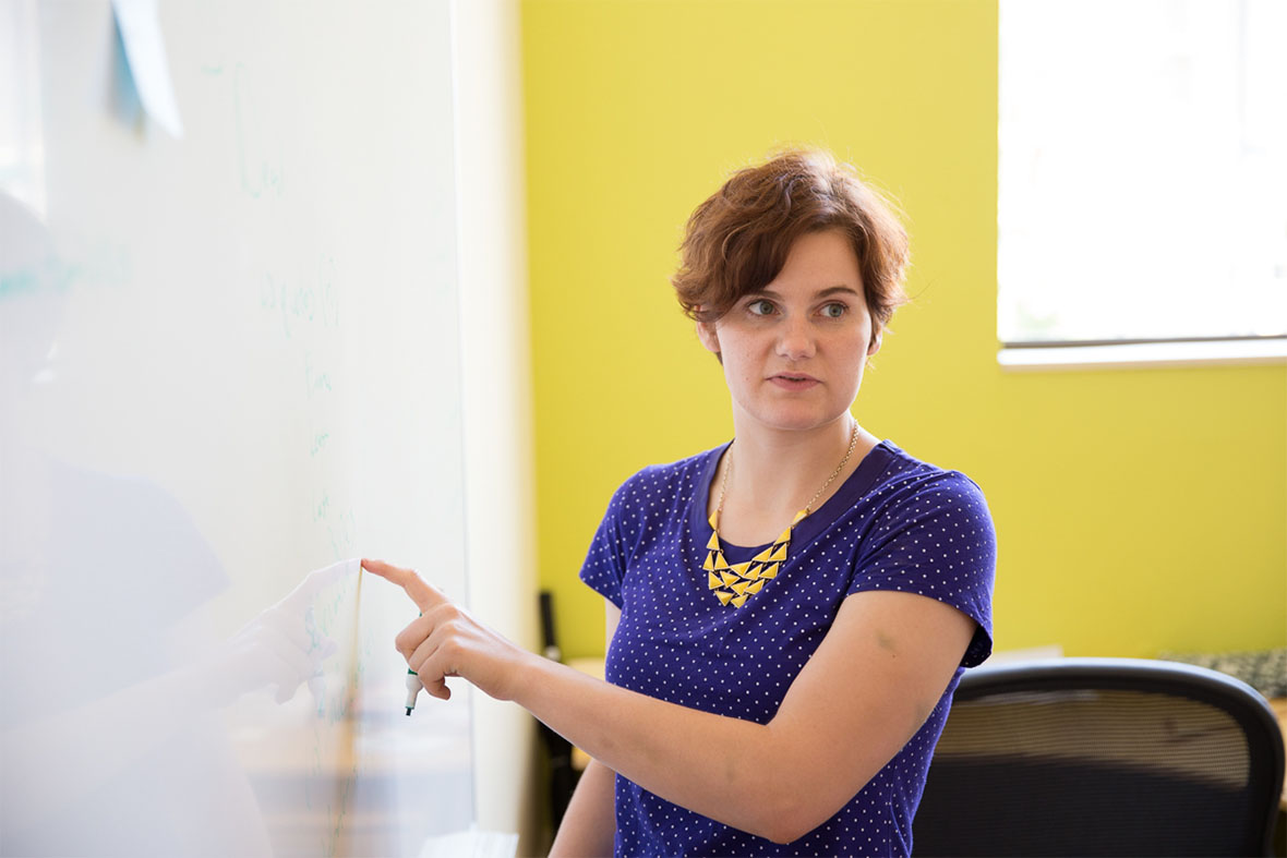 A photo of Jeanette Head discussing software using a white board at Atomic Object