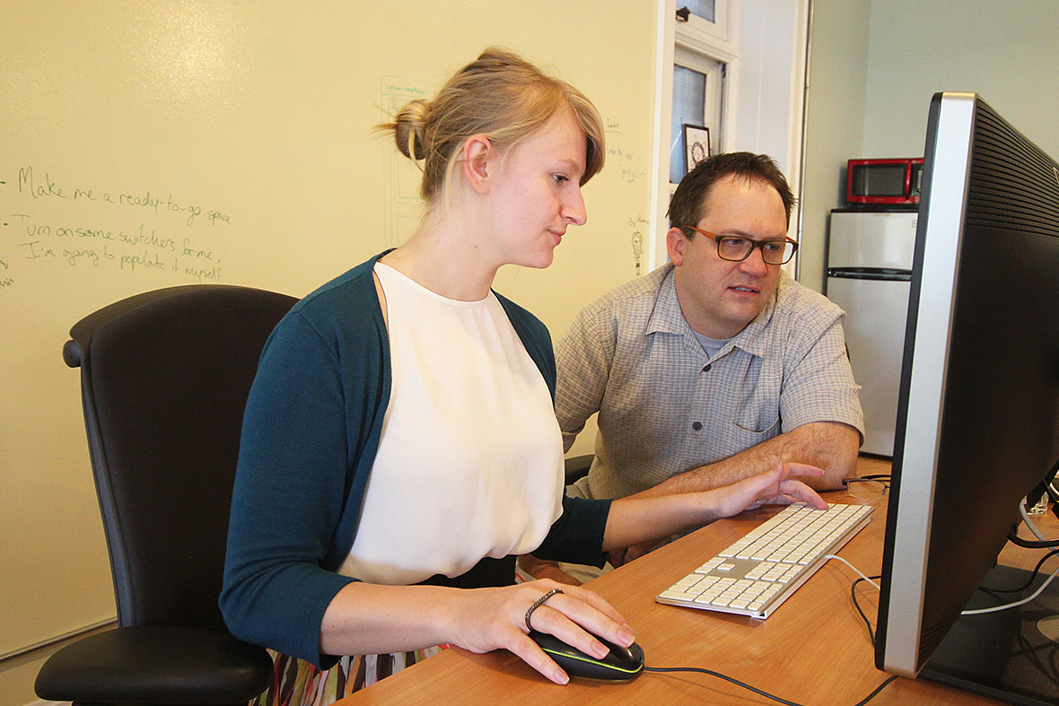 A photo of Rachael Miller and Greg Williams working together at a computer