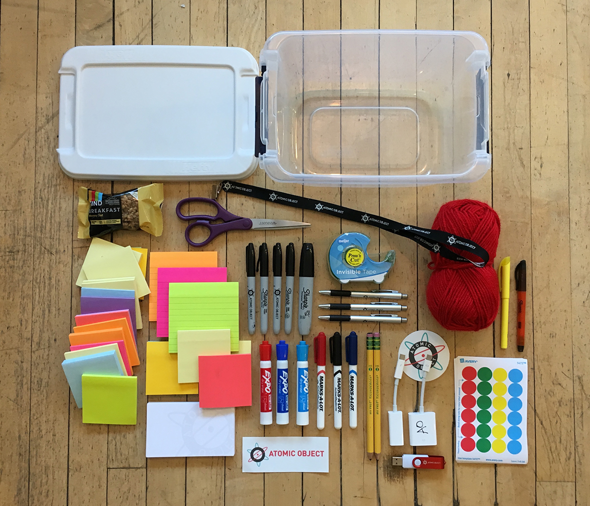 Picture of prototyping supplies: post-it notes, pens, scissors, stickers, yarn, tape, etc.