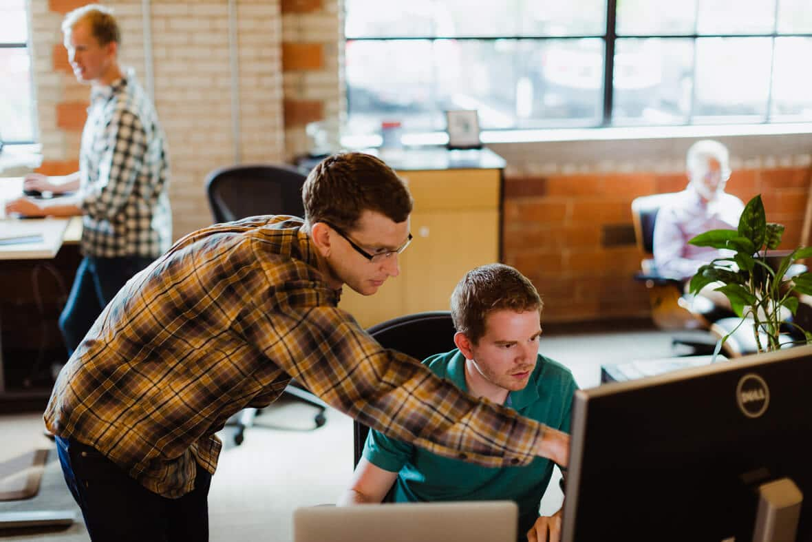 Two men working together at a computer