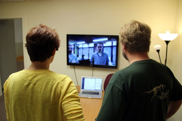 Two developers stand in front of a large monitor, conversing with two other developers via a video call.