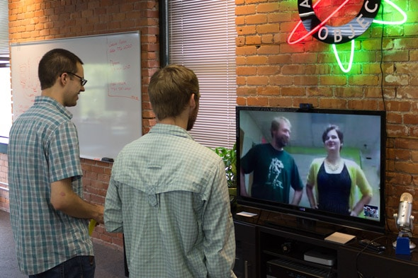 Two developers standing in front of a large monitor, having a remote video call with two other developers.