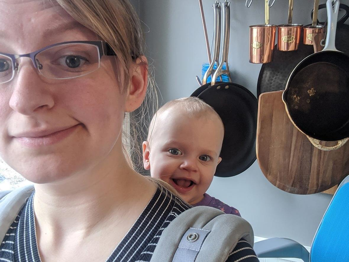 Woman in Kitchen with Baby in Backpack